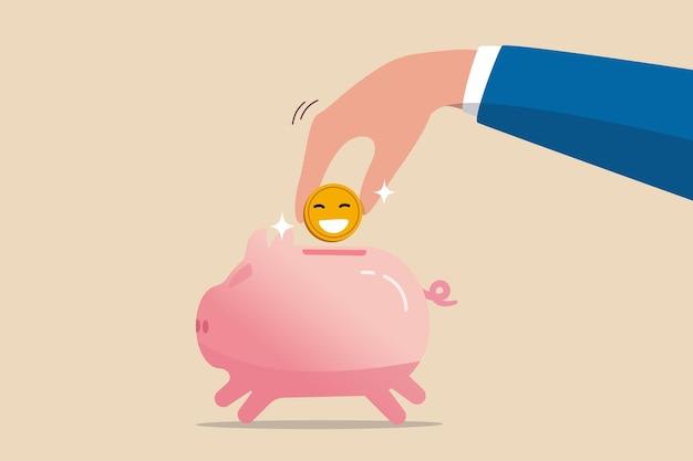 Dinheiro para comprar felicidade, economizar para uma aposentadoria feliz ou pagar por um conceito de estilo de vida feliz, mão segurando uma moeda dourada brilhante com um rosto sorridente feliz colocado no cofrinho rosa.