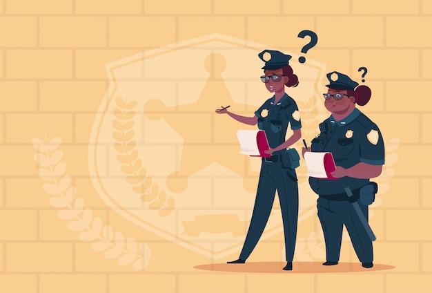 Dois, americano africano, polícia, mulheres, segurando, caixas, com, escritório pessoal, demitido, desgastar, uniforme feminino, guardas, ligado, azul, tijolos, fundo
