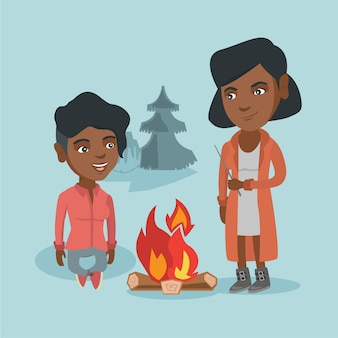 Dois amigos que sentam-se em torno da fogueira no acampamento.