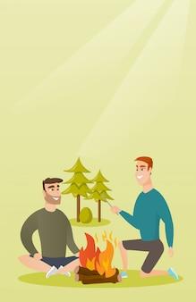 Dois amigos sentados ao redor da fogueira no acampamento