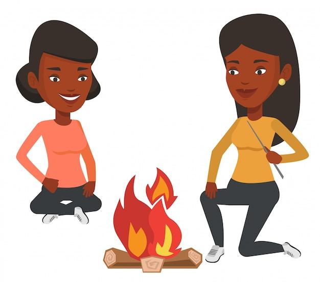 Dois amigos sentados ao redor da fogueira no camping.
