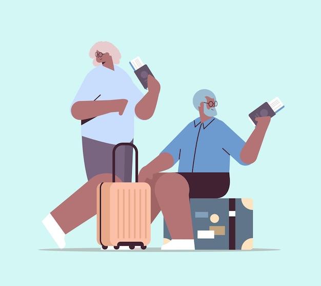 Dois avós idosos de turistas com bagagem segurando passaportes e passagens prontas para embarque no aeroporto