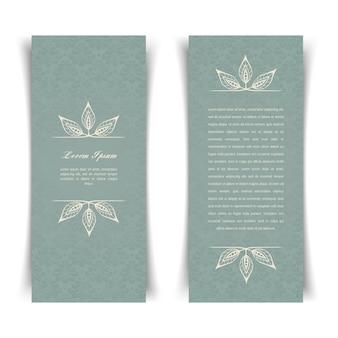 Dois cartões vintage cinza-azulados verticais com elementos de design floral
