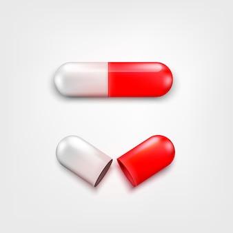 Dois comprimidos da cápsula brancos e cor vermelha no fundo branco. um aberto e fechado. fundo para loja de farmácia ou drogaria. elemento de conceito médico ou farmacêutico