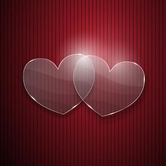 Dois corações de vidro em fundo vermelho listrado