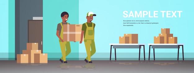 Dois correios em uniforme carregando caixa de papelão pacote correio expresso serviço de entrega conceito operários industriais trabalhando no estoque do armazém comprimento total horizontal
