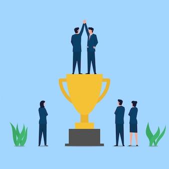 Dois empresário alto cinco acima do troféu, a metáfora de sucesso e cooperação.