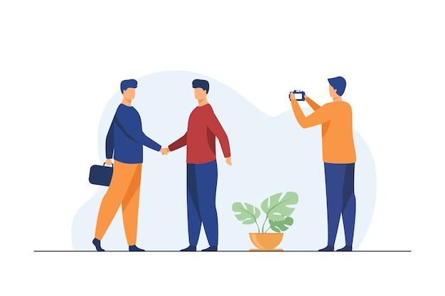 Dois empresários apertando as mãos e outro homem tirando foto.