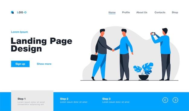 Dois empresários apertando as mãos e outro tirando foto do modelo da página de destino