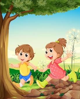 Dois filhos adoráveis brincando debaixo da árvore
