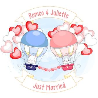 Dois gatinhos fofos em balões de ar quente, rodeados por balões de coração