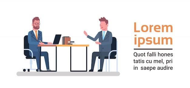 Dois homens de negócio que sentam-se na mesa de escritório que fala a reunião da sessão de reflexão ou o conceito da entrevista