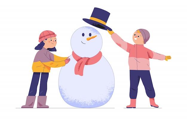 Dois meninos e uma menina jogam estátuas de bolas de neve durante as férias e o inverno
