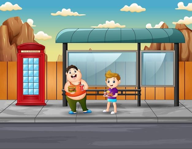 Dois meninos fofos segurando comidas no ponto de ônibus