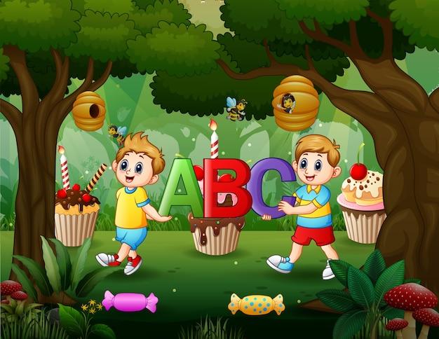 Dois meninos segurando a letra abc na floresta doce
