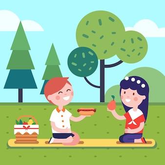 Dois miúdos que almoçam piquenique na grama do parque