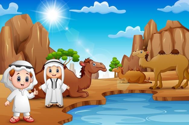 Dois rapazes árabes com camelos no deserto