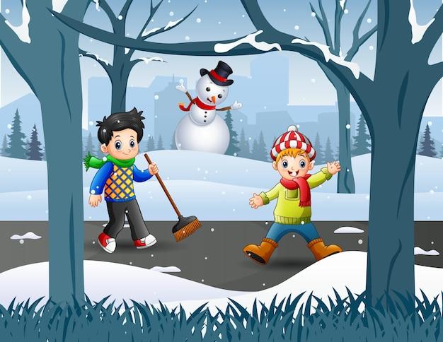 Dois rapazes limpando neve na estrada
