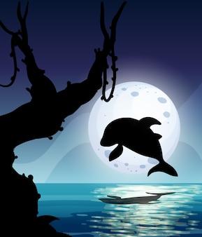 Dolphin siluete pulando no mar à noite