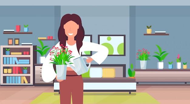 Dona de casa menina cute rega flor no pote mulher feliz cuidando do conceito de planta em vaso moderno apartamento casa retrato interior quarto horizontal