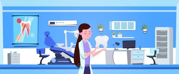 Doutor mulher, segurando, dente, sobre, escritório dental, interior, odontólogo, hospitalar