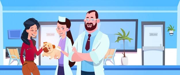 Doutores do veterinário que dão o cão saudável ao proprietário feliz no conceito da medicina veterinária do escritório da clínica