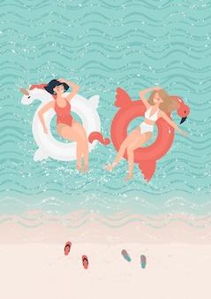 Duas amigas em círculos de natação no mar perto da praia