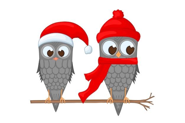Duas corujas no galho com o chapéu e lenço de papai noel. postal de ano novo e natal.