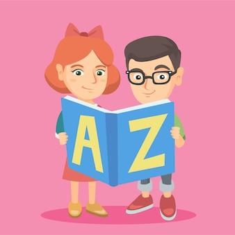 Duas crianças caucasianas estudando com um livro-abc.