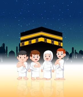 Duas crianças com seus pais estão fazendo peregrinação na frente de ka'bah