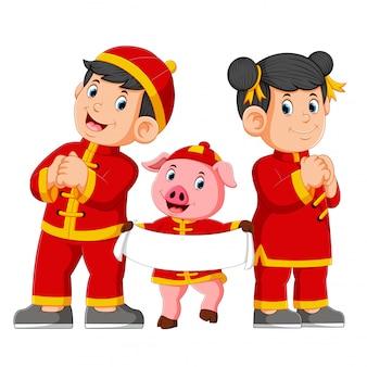 Duas crianças com um porco rosa estão dando uma saudação para o ano novo de uma china