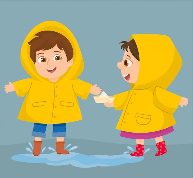 Duas crianças engraçadas felizes sob o chuveiro de outono