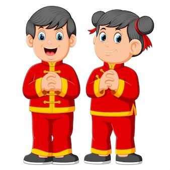Duas crianças estão dando uma saudação para o ano novo de um chinês