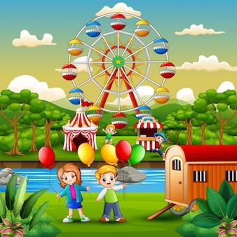 Duas crianças, segurando, um, balões, e, tendo divertimento, em, parque divertimento