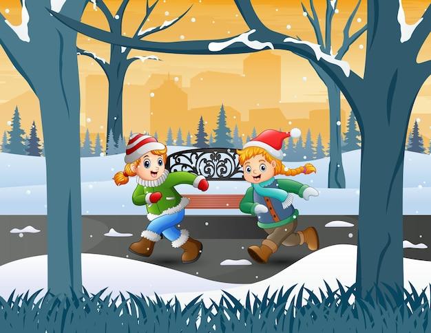 Duas garotas correndo na paisagem do parque de inverno