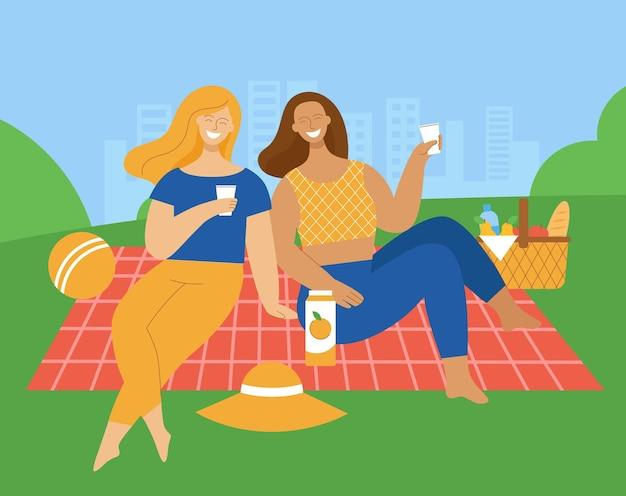 Duas jovens estão sentadas em uma manta em um parque. amigos estão rindo e conversando