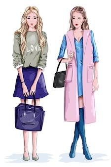 Duas lindas garotas elegantes com bolsas