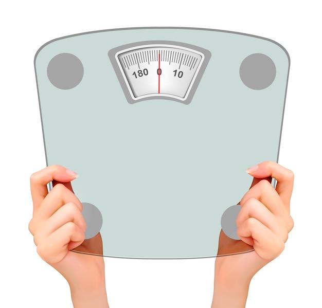 Duas mãos segurando uma balança. conceito de dieta.