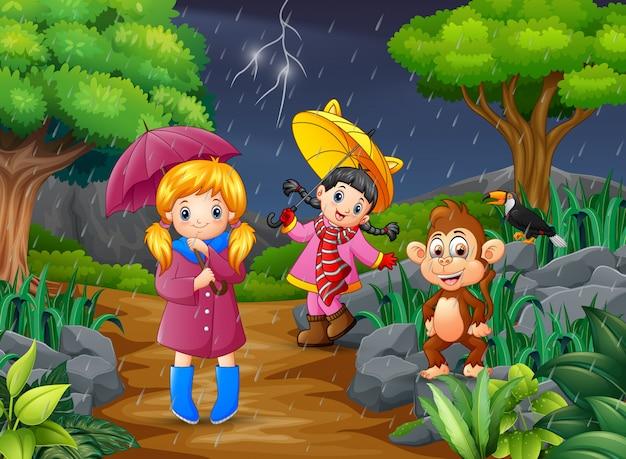 Duas menina carregando guarda-chuva vai sob uma chuva com macaco