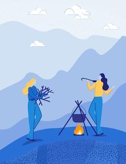 Duas mulheres cozinham comida na fogueira na viagem de acampamento.