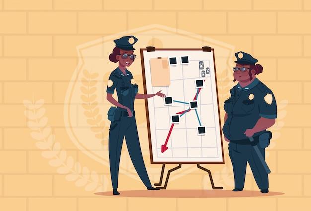 Duas mulheres da polícia americana africano, planejando a ação no quadro branco usando uniforme de guardas femininas na blue tijolos fundo