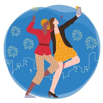 Duas mulheres festejam juntas enquanto tiram selfies e seguram fogos de artifício em um cenário de fogos de artifício e a cidade à noite