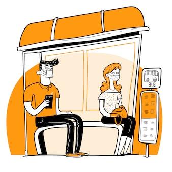 Duas pessoas com máscara, sentado em uma parada de ônibus