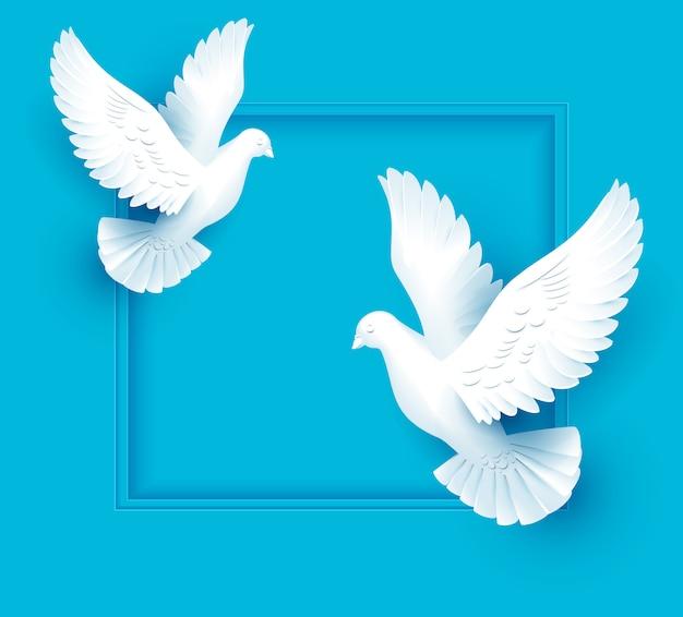Duas pombas brancas voam sobre fundo azul