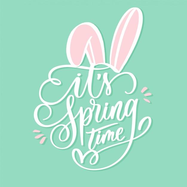 É tempo de primavera letras inscrição com orelhas de coelho.