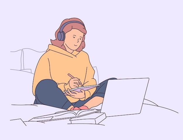 Educação, estudo, conceito de aprendizagem. menina estudando na cama com laptop e livros.