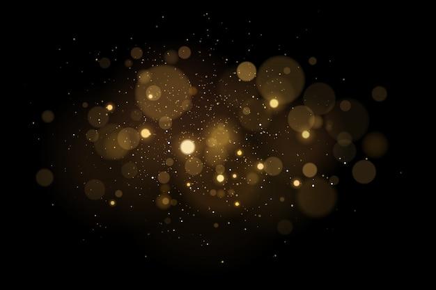 Efeito de luz mágico abstrato com bokeh brilhos dourados sobre um fundo preto. luzes de natal. pó voador brilhante.