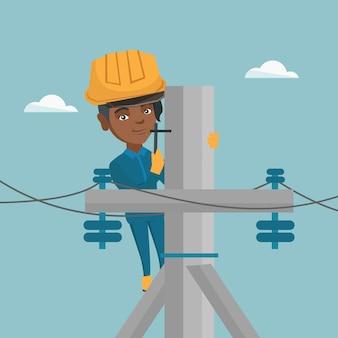 Eletricista africana trabalhando em poste de energia elétrica