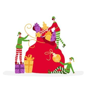 Elfos em miniatura de natal estão embalando uma grande sacola de presentes