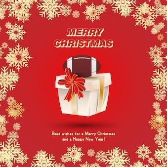 Embalagem de presente com uma bola de futebol americano e fitas de ouro e um laço vermelho no fundo dos flocos de neve. cartão festivo de natal e ano novo